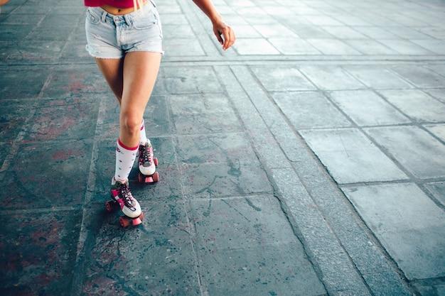Uma foto de pernas bem construídas e magras de menina. ela está posando. a menina está mantendo a perna direita atrás da esquerda.