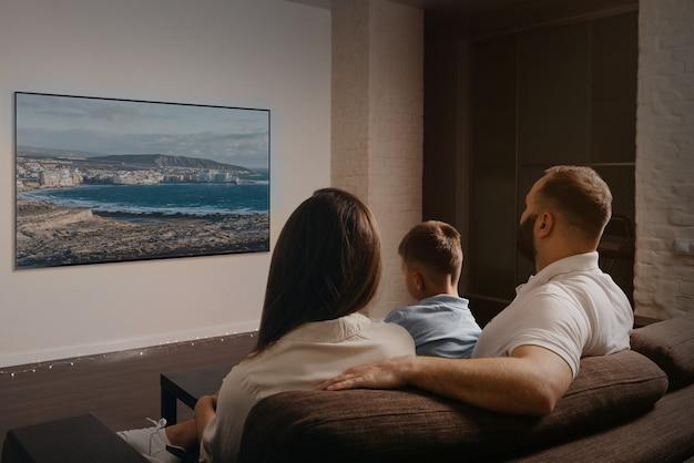 Uma foto de trás de um pai com barba, um filho e uma jovem mãe que estão assistindo a um filme em uma televisão widescreen no sofá