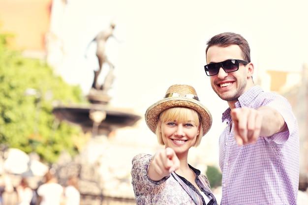 Uma foto de turistas felizes apontando para a câmera em frente à fonte de neptun em gdansk, na polônia