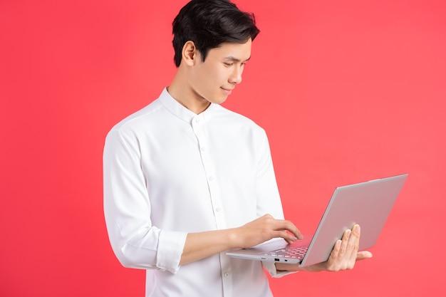 Uma foto de um homem asiático bonito parado em uma parede vermelha com um computador