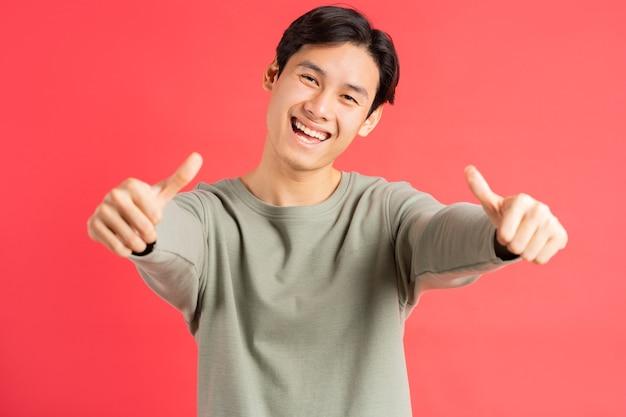 Uma foto de um homem asiático bonito segurando dois polegares com um rosto alegre