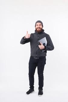 Uma foto de um homem simpático segurando seu computador e mostrando o polegar