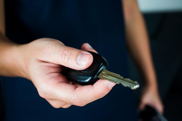 Uma foto de um homem vestindo uma camisa preta, segurando uma chave de carro.