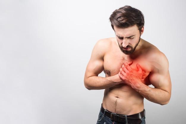 Uma foto de um jovem e bonito com uma dor no peito no peito. é bastante incomum para sua idade ter esse tipo de dor. ele está quase em agonia. também há um ponto vermelho em seu peito. isolado