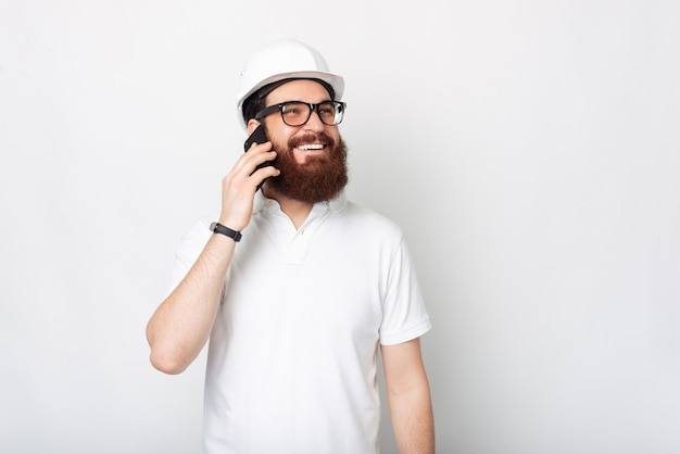 Uma foto de um jovem engenheiro barbudo falando com seu telefone, sorrindo e em pé perto de uma parede branca