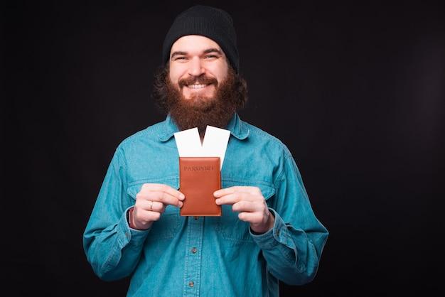 Uma foto de um jovem positivo segurando um passaporte e alguns bilhetes de avião perto de uma parede preta