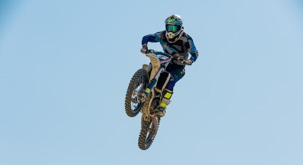 Uma foto de um motociclista fazendo um truque e pula no ar