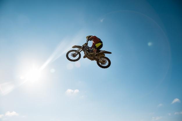 Uma foto de um motociclista fazendo uma acrobacia e pula no ar