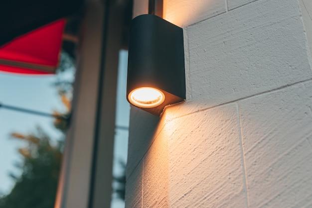 Uma foto de um poste de luz em um prédio moderno iluminando as paredes externas da construção à noite