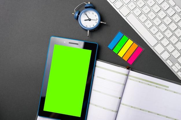 Uma foto de um tablet perto de um diário, um pequeno relógio e um teclado em uma mesa