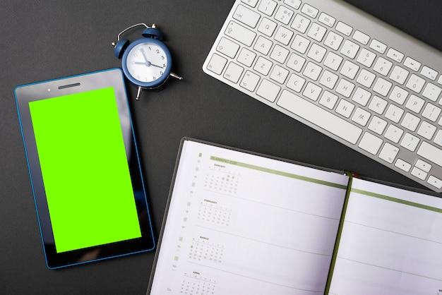Uma foto de uma composição de um novo tablet em uma mesa e aplanner um pequeno relógio e um teclado