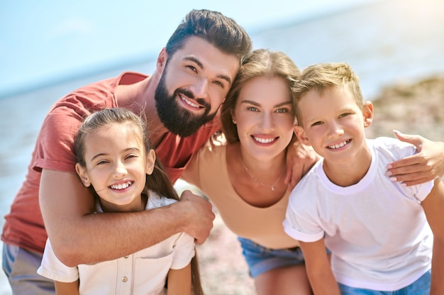 Uma foto de uma família feliz e sorridente se divertindo em uma praia