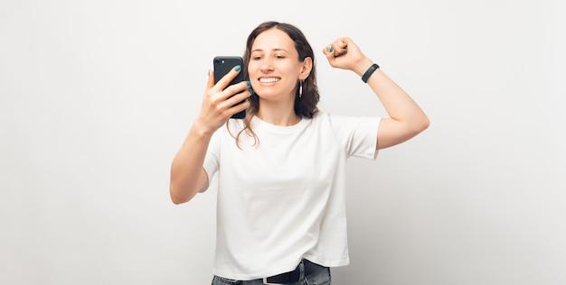 Uma foto de uma jovem excitada olhando para o telefone, vencendo o jogo
