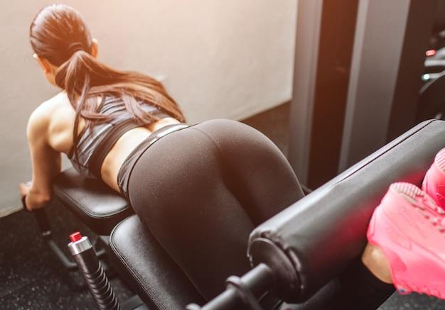 Uma foto de uma linda garota fazendo flexões na máquina