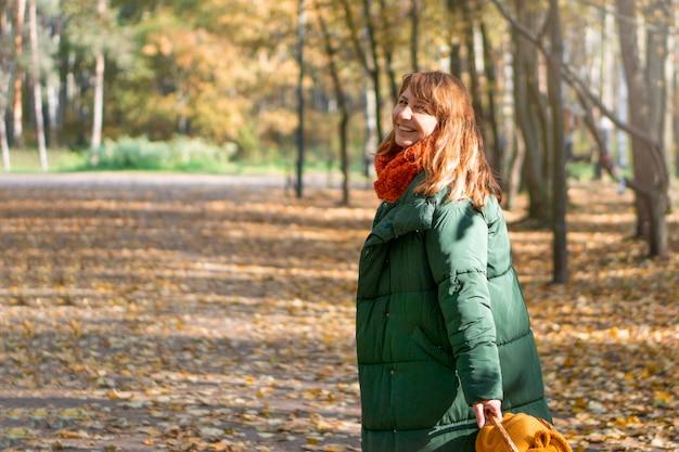 Uma foto de uma linda morena sorrindo para a câmera, folhas caindo amareladas, uma caminhada e um lindo perfume inesquecível de outono, um parque da cidade, na rua.