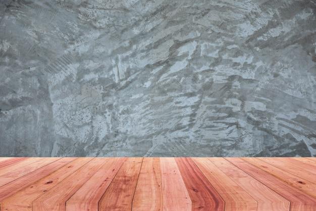 Uma foto de uma mesa de madeira na frente de um fundo desfocado abstrato de um cimento polido