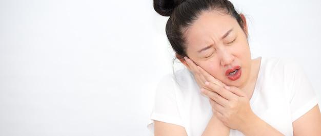 Uma foto de uma mulher com dor de dente, colocando a mão na bochecha, dor, tendo problemas de saúde bucal e cuidando do dentista.