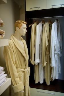 Uma foto de vários roupões em cabides de madeira em uma loja e um manequim masculino em um curativo