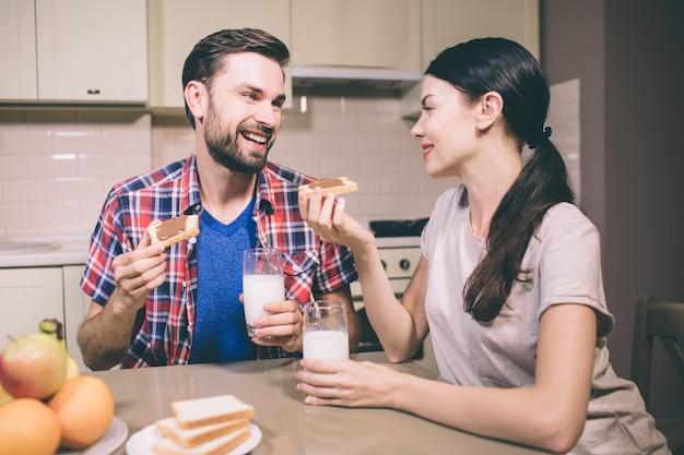 Uma foto do belo casal se senta à mesa e se entreolha. eles fazem torradas com pasta de chocolate. também há copos de leite nas mãos. as pessoas parecem felizes.