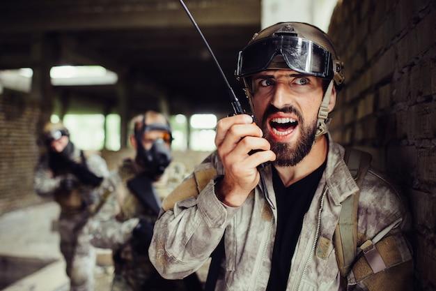 Uma foto do cara em pé e encostado na parede. ele está falando com um rádio portátil. seus lutadores estão atrás dele e prontos para atacar a qualquer momento. eles têm espingardas nas mãos.