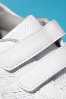 Uma foto do close up do fecho de velcro de tênis branco para crianças de tênis feito de couro com ...