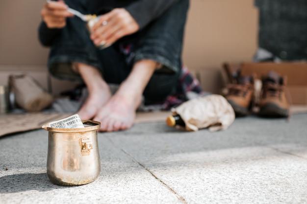 Uma foto do copo em pé no chão de concreto. há um dólar nele. também podemos ver as pernas do mendigo. ele está segurando uma lata com comida nas mãos e colher também. há muitas coisas no chão