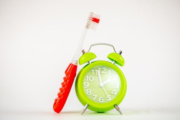 Uma foto do despertador e da escova de dentes verdes.