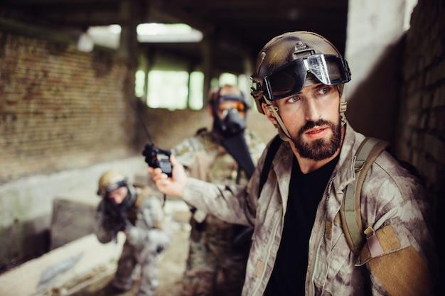 Uma foto do guerreiro em pé e encostado na parede. ele está olhando para fora. guy é muito cuidadoso. ele está mostrando o sinal de parada para seus soldados. homem tem uniforme especial e óculos na testa.