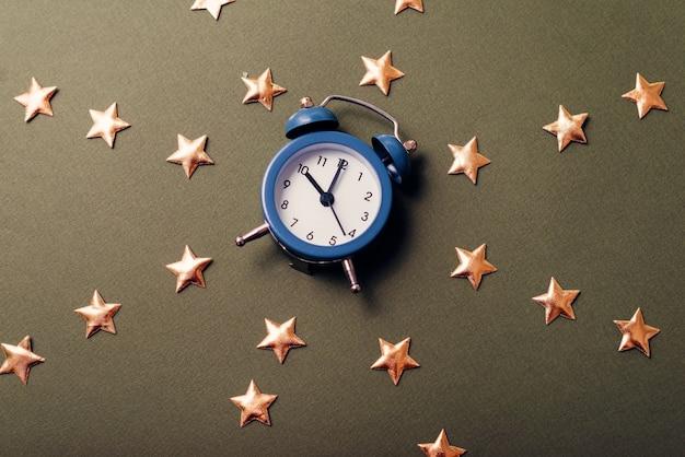 Uma foto em close-up de um pequeno relógio azul entre várias estrelas em uma mesa escura