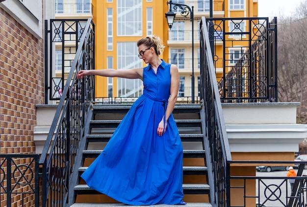 Uma foto em tamanho real de uma mulher atraente em um vestido longo de salto alto no fundo da parede de tijolo. a mulher de óculos posa para um fotógrafo.
