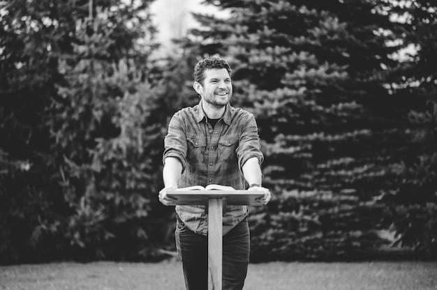 Uma foto em tons de cinza de um homem em pé perto do pódio e sorrindo