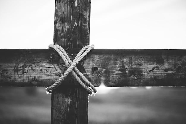 Uma foto em tons de cinza de uma cruz de madeira feita à mão