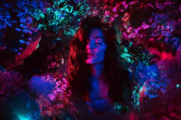 Uma foto fantástica de uma menina em flores com luz neon multicolorida e fantasmagoria. o conceito de fantasia, contos de fadas, magia e fadas.