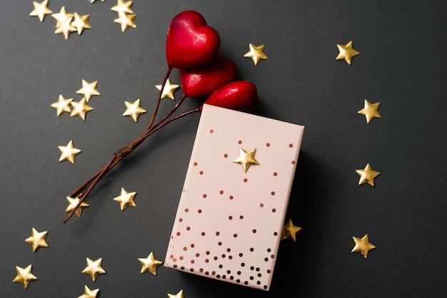 Uma foto fofa de um presente embrulhado perto de algumas estrelas e alguns corações vermelhos como decoração