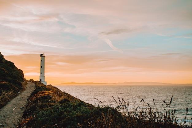 Uma foto horizontal do farol branco durante o pôr do sol