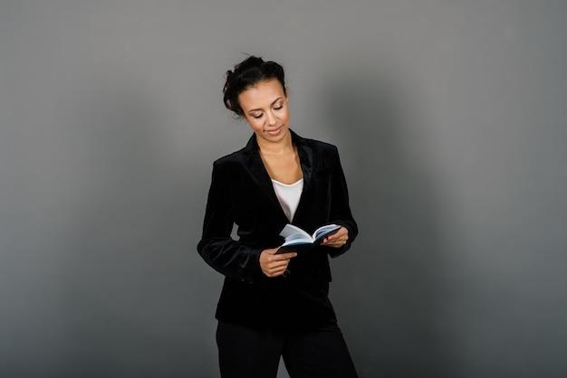 Uma foto isolada de uma mulher de negócios negra feliz em estúdio, notebook, smartphone