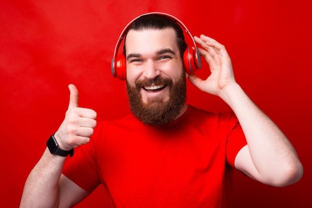 Uma foto onde um homem de barba mostra que gosta da música que está ouvindo nos fones de ouvido