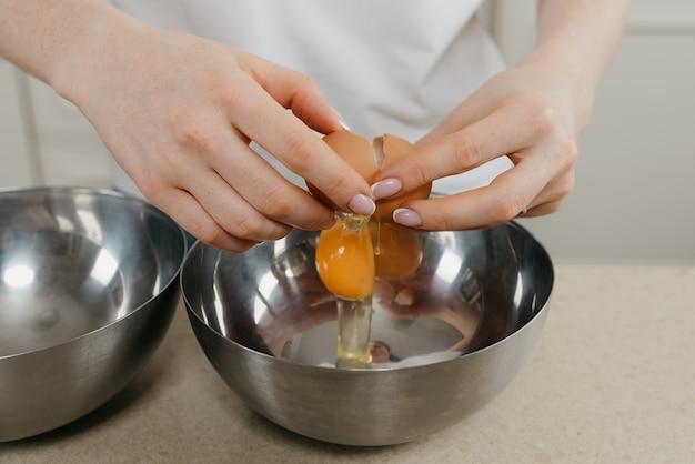 Uma foto próxima das mãos de uma jovem quebrando um ovo acima da tigela de aço inoxidável na cozinha