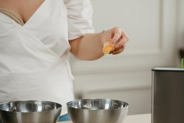 Uma foto próxima das mãos de uma jovem separando a gema da clara do ovo acima da tigela de aço inoxidável na cozinha