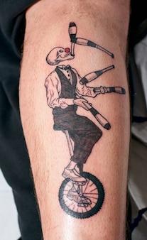 Uma foto vertical da perna de um homem com uma tatuagem de esqueleto em um terno malabarismo em uma roda