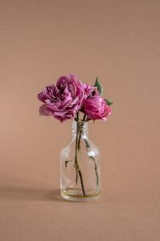 Uma foto vertical de lindas rosas secas em um pequeno vaso na vista lateral do plano de fundo marrom