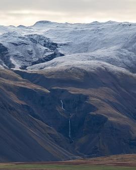 Uma foto vertical de montanhas com neve no topo