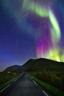 Uma foto vertical de uma estrada vazia sob um céu cheio de estrelas azuis
