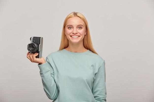 Uma fotógrafa adorável parece feliz sorrindo, segurando uma câmera fotográfica retro vintage em uma das mãos
