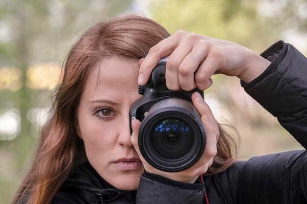 Uma fotógrafa fotojornalista ruiva bonita segura uma câmera nas mãos e olha para a lente e o visualizador. retrato, rosto close-up