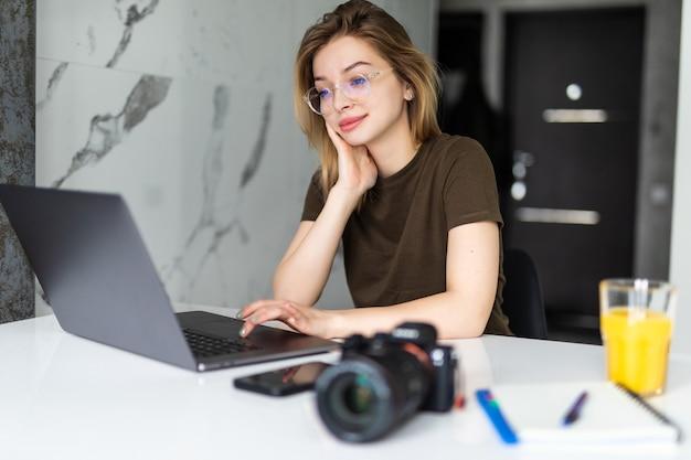 Uma fotógrafa jovem e bonita processando imagens em um laptop, olhando para a câmera fotográfica em casa