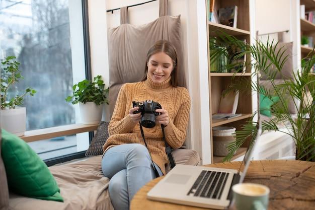 Uma fotógrafa sorridente editando suas fotos