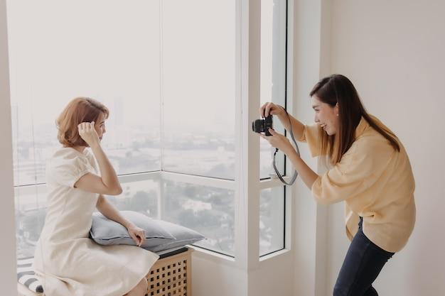 Uma fotógrafa tirando uma foto de sua modelo feminina