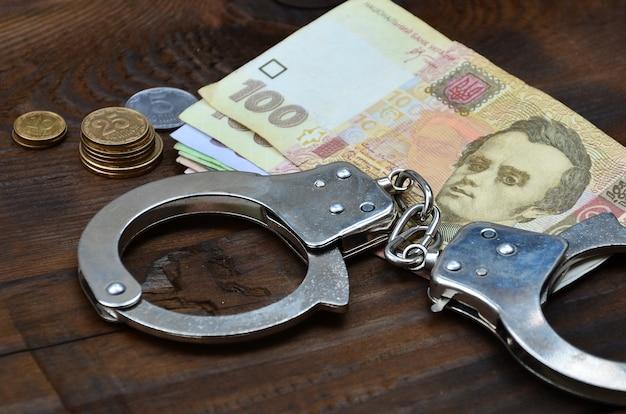 Uma fotografia de uma certa quantia de dinheiro ucraniano e algemas policiais.