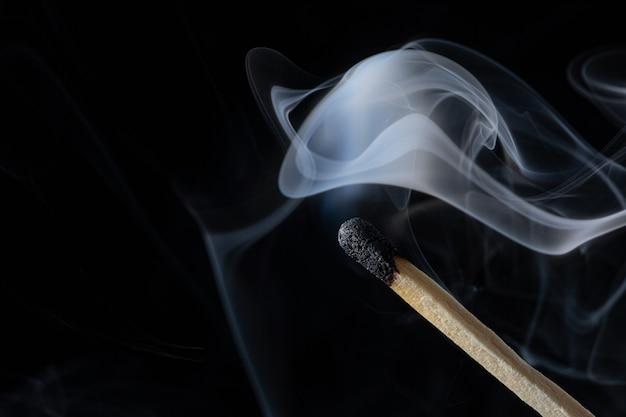 Uma fotografia macro de um palito de fósforo com fumaça